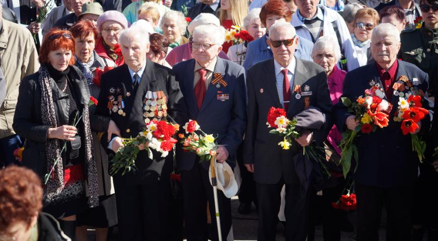 Люди несут цветы к Памятнику Освободителям